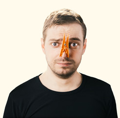 Portrait of  man with clothespin on his nose. Toned image.