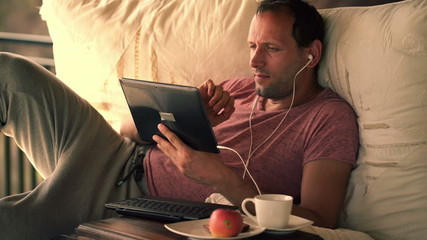 Young man watching movie on tablet computer, lying on gazebo bed