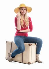 Blonde Frau sitzt auf einem Koffer