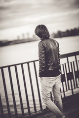 Young beautiful short hair woman at the embankment in autumn eve