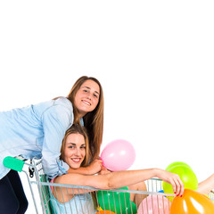 Friends playing with balloons and supermarket cart