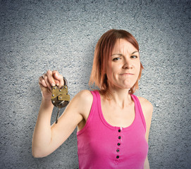 Redhead girl holding vintage padlock over textured background