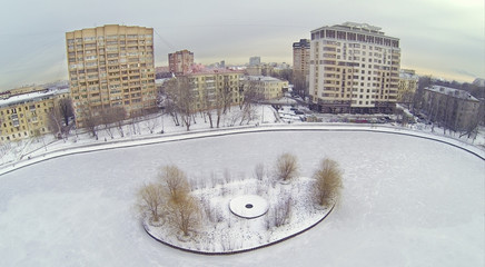 Small island on pond in winter cloudy day in Moscow