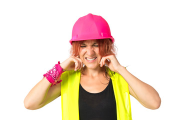 Worker woman covering her ears over white background
