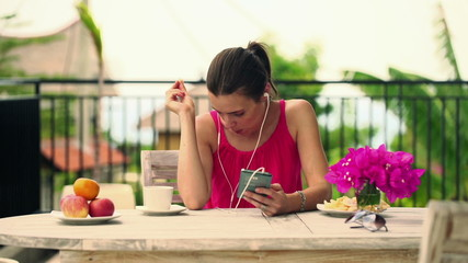 Happy pretty woman listen to music on her smartphone on terrace