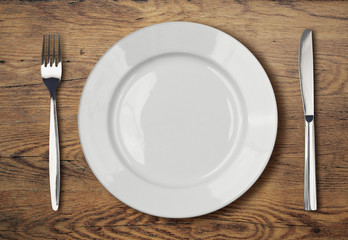 white empty dinner plate setting on wooden table