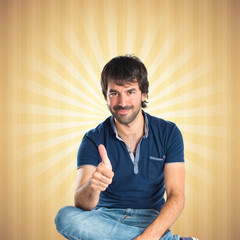 Man with thumb up over pop background