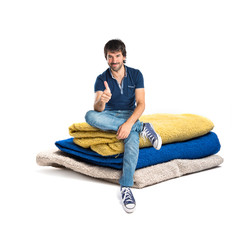 Man with thumb up sitting on towels