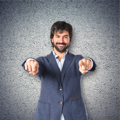 Businessman pointing to the front over textured background