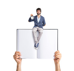 Man holding a clock sitting on book