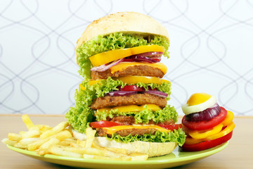 big hamburger with french fries and salad