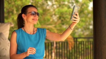Cute woman taking selfie photo with cellphone on terrace