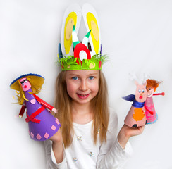 Girl demonstrating her cruft work, Easter bonnet and paper dolls
