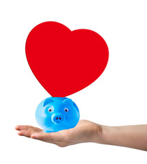 Piggy bank with red paper shape heart on hand