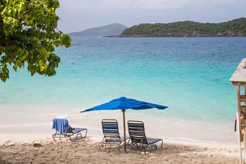 Chaise Lounges Under Blue Umbrella on Tropical Beach