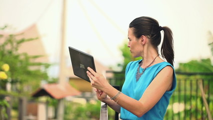 Young woman chatting on tablet computer on terrace
