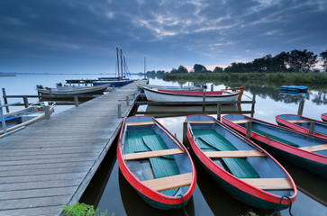 boats on lake harbor in dusk