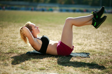 Young woman doing press fitness exercise for stomach muscles