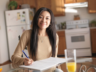 african american teen in kitchen studying and smiling at camera
