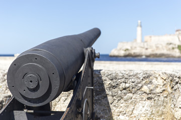 Old canon pointing at the lighthouse in Havana, Cuba