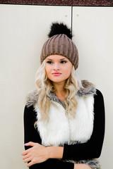 Красивая девушка  блондинка в шапке и жилете