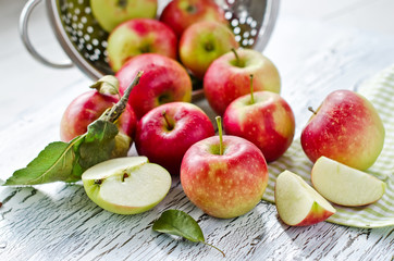 Red fresh apples from garden with leaves on wooden background