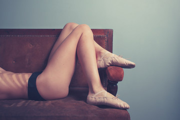 Young woman wearing ballet slippers on sofa