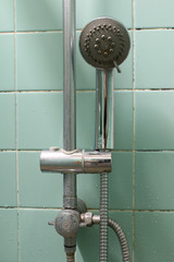 Shower on the holder on green tile wall.