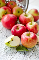 Juicy fresh apples from garden with leaves on wooden background