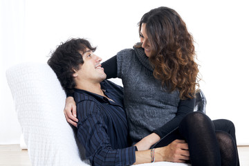 Happy couple lying down in bedroom watching television together