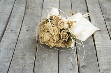 Dried yellow roses on gray old table
