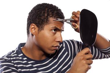 dark-skinned boy haircut himself with scissors