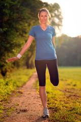 Junge Frau dehnt und stretcht ihre Oberschenkelmuskulatur