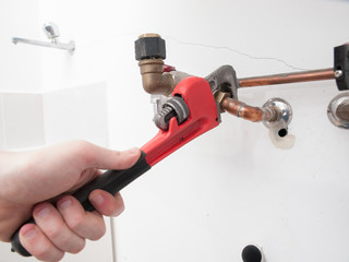 Hands repairing the plumbing pipes of an electric boiler