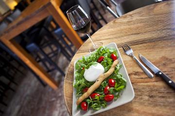 Mozzarella, salad and tomato, glass of red wine in a bistro