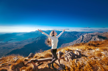 Happy freedom woman with opened arms, on the top of a mountain,