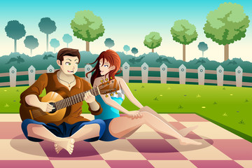 Couple playing guitar together in a park