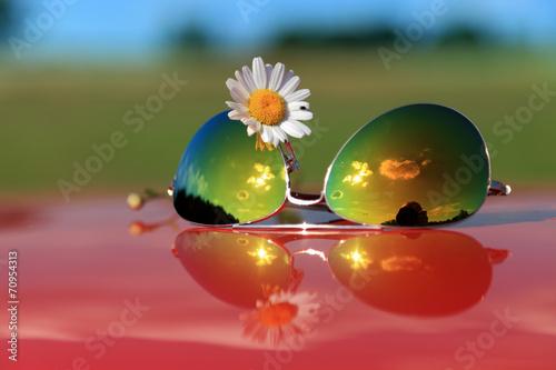 Okulary przeciwsłoneczne i biały kwiatek z odbiciem. - 70954313