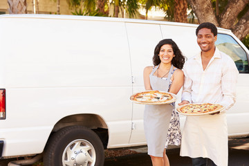 Couple Delivering Pizza Standing In Front Of Van