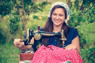 Smiling woman with vintage hand sewing machine