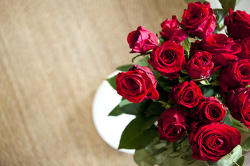 Bunch of red roses on a wooden floor