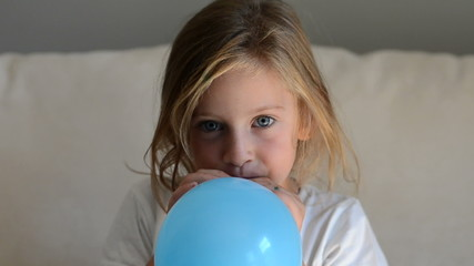 Girl inflating a blue balloon