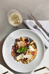 Pasta, parmesan and vegetables on a plate, glass of white wine