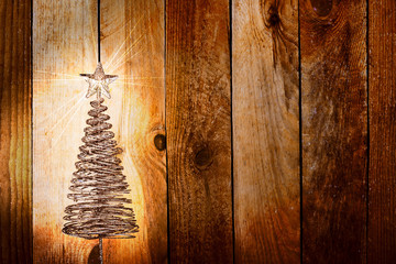 Christmas greeting card with gold metal firtree on the wooden ba