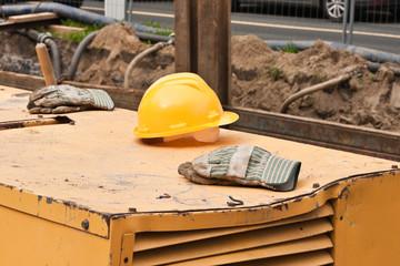 Ein Schutzhelm und Arbeitshandschuhe liegen auf einer Maschine
