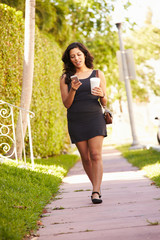 Woman Walking Along Street To Work Using Mobile Phone
