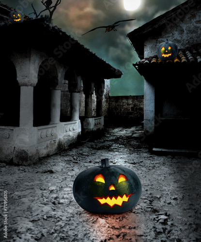Halloween pumpkins in the yard of an old house at night in the b