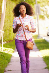 Woman Walking Along Street To Work Listening To Music