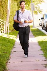 Man Walking Along Street To Work Listening To Music
