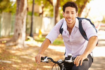 Young Man Cycling Along Street To Work